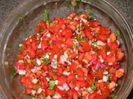Pomidory pozbawione skórki i pestek kroimy w kostkę i mieszamy w misce z sosem pomidorowym, posiekanym czosnkiem, cebulą i chill...