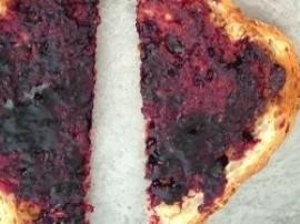 Dwie kromki chleba tostowego włożyć do tostera. Po upieczeniu tostów, posmarować tosty dżemem wiśniowym. Na koniec pokroić banan...